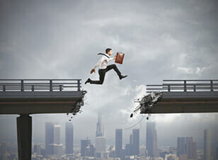Business man jumping over broken bridge