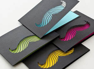 black cards with coloured moustache cut outs