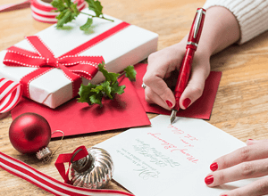 writing a message in a christmas card next to christmas presents