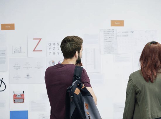man and women working together as a team looking at a whiteboard