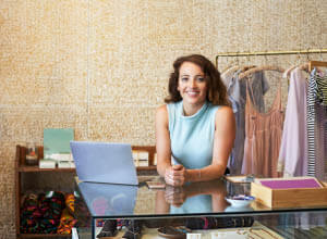 woman leaning on shop front counter